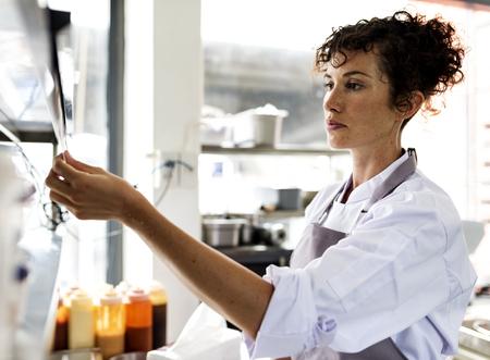 Keukenpersoneel die voedselbestellingen leest Stockfoto