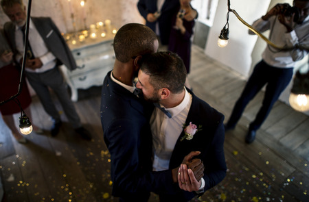 Newlywed gay couple groom dancing