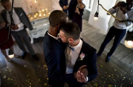 Newlywed gay couple groom dancing
