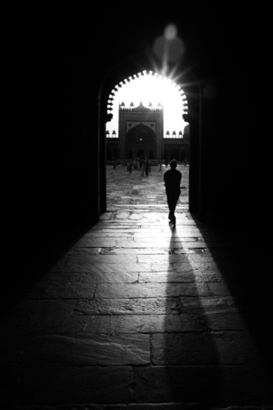 Silhouette of man walking through a mosque.