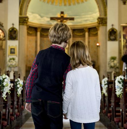 Children praying together inside a church