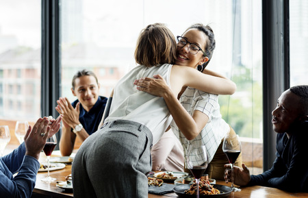 Couple of friends are hugging during lunch