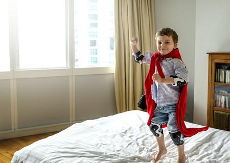 ベッドでスーパーヒーローを演じる少年 写真素材