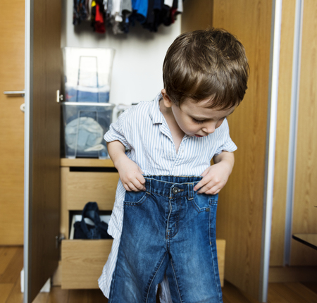 Liitle boy getting dressed by himself