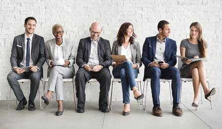 Grupa różnorodnych osób czeka na rozmowę kwalifikacyjną