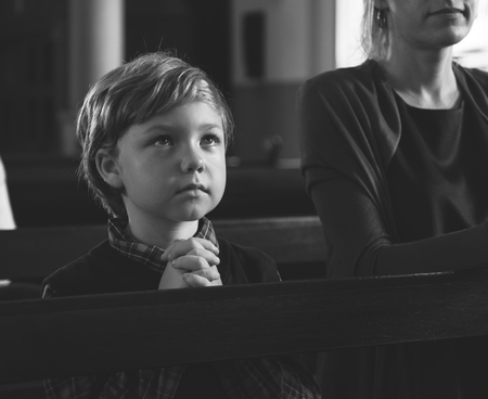 Kleiner Junge, der innerhalb einer Kirche betet Standard-Bild - 89996992