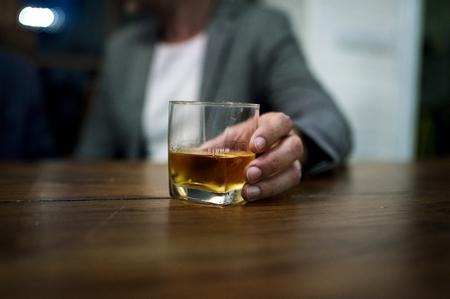 アルコールのガラスを運ぶ人のショット 写真素材