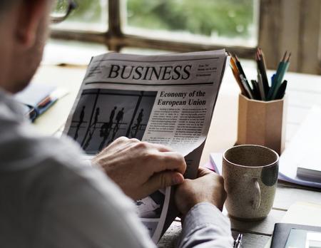 彼の机で新聞を読んでいる人