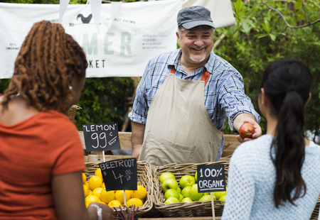 Greengrocer selling organic fresh agricultural product at farmer market Stok Fotoğraf - 90595748