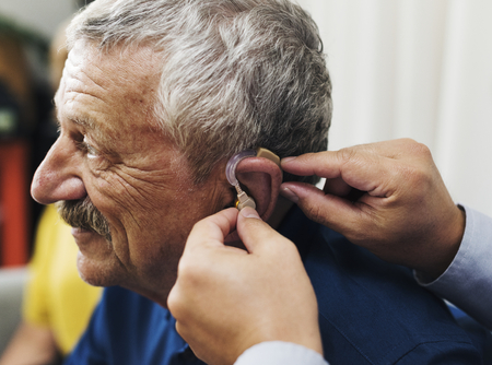Doctor inserting hearing aid to patient's ear