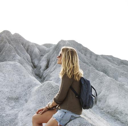 女性は、岩の上のハイキングから休息を取る