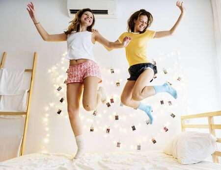 Two Caucasian women jumping on the bed together Stock Photo