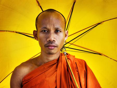 Buddhist monk holding an umbrella
