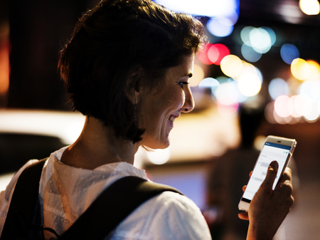 An Adult Woman Using Mobile Phone at Night Time Stock Photo