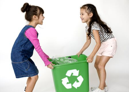 Two little girls moving a recycle box