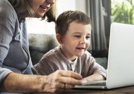 Großmutter und Enkel, die zusammen den Laptop verwenden Standard-Bild - 90615448