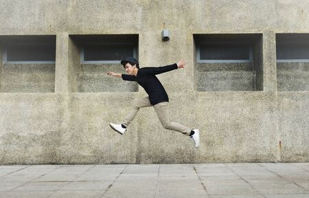Asian guy midair jumpshot outdoors