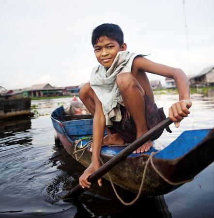 보트 부동 마을에서 여행하는 소년.