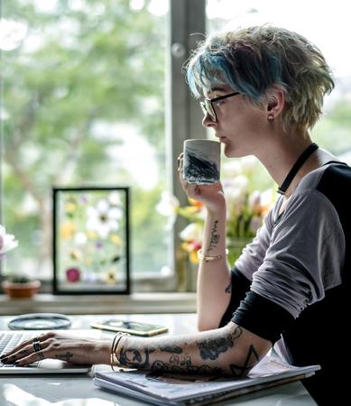여자가 그녀의 노트북에서 작업하고 커피를 마시는