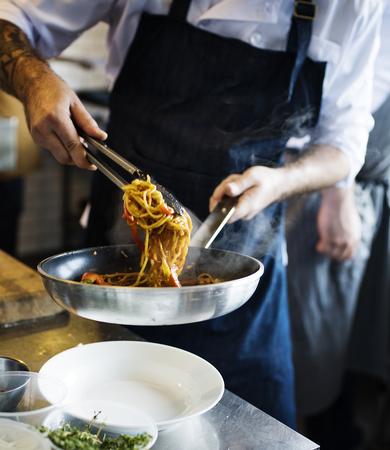 キッチンでシェフがスパゲッティを調理 写真素材 - 90667105