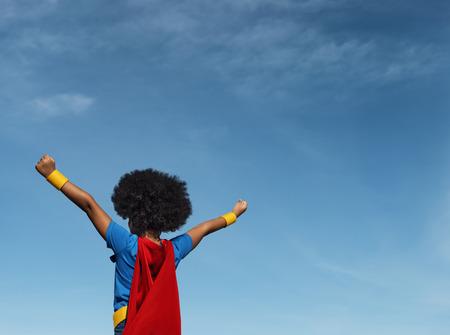 Mädchen mit Afro, der Superheld spielt Standard-Bild