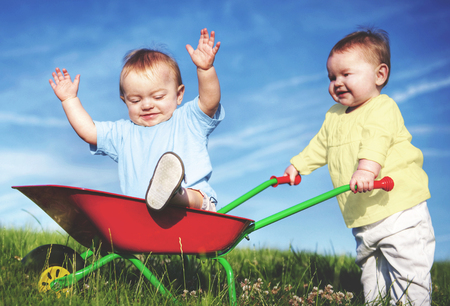 Two toddlers are playing together outdoors. Stok Fotoğraf