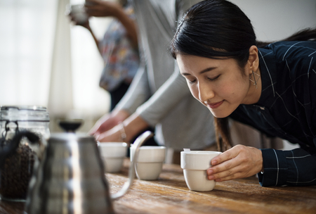 Woman smelling the aroma of a cup of coffee Stock fotó