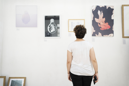 Woman looking at pictures on a wall Stok Fotoğraf