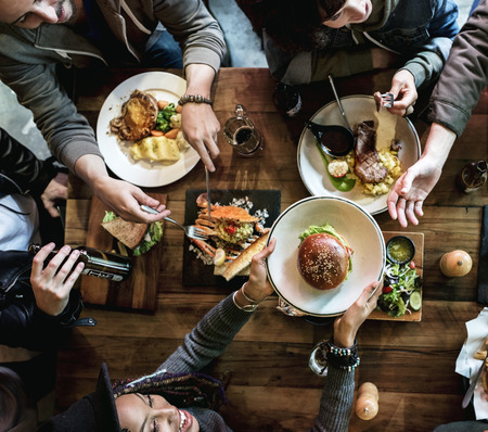 Group of friends eating together Stock Photo