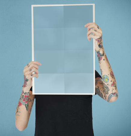 Tattooed woman holding a blank paper