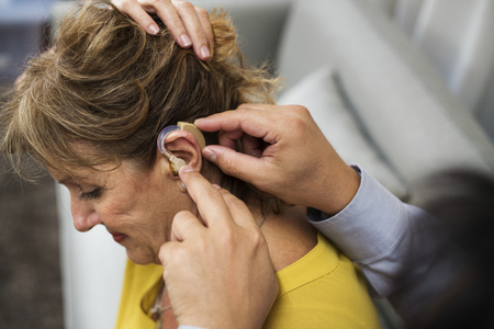 A doctor inserting hearing aid to a patient's ear Stock Photo - 90673337