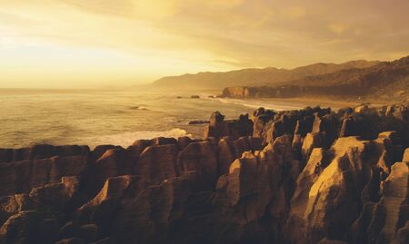 Panaroma of pancake rocks in the scenic view of mountains, beach and sunset.
