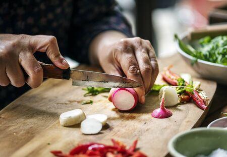 Hands using a knife chopping turnips Фото со стока