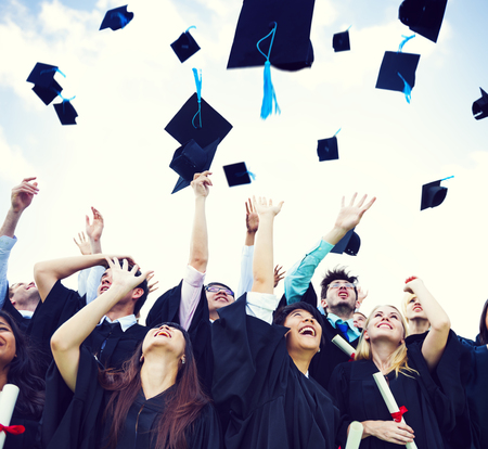 Graduating students throwing hats in the air Stock Photo