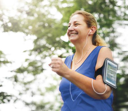 Mature woman jogging in the park Фото со стока
