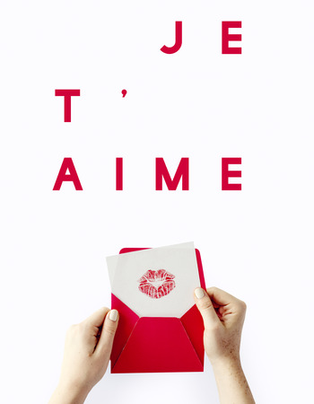 Je Taime text over a woman holding a love letter Stock Photo