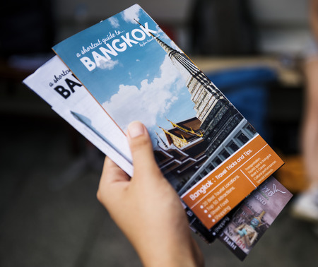Closeup of hand holding Bangkok travel guide brochure Foto de archivo