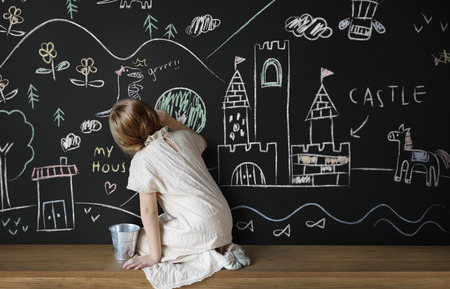 Little girl drawing on a blackboard