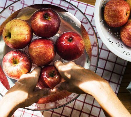 그릇에 사과를 세척하는 손의 공중보기