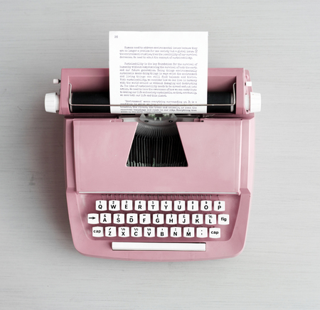 Retro pastel typewriter on grey surface Stock Photo