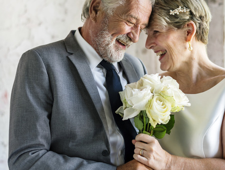 Senior Couple with White Roses Flower Bouqet Imagens