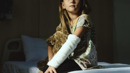 Junges kaukasisches Mädchen mit der Gipsform des gebrochenen Armes