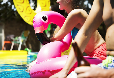 A diverse group of friends enjoying summer time by the pool with inflatable floats 스톡 콘텐츠