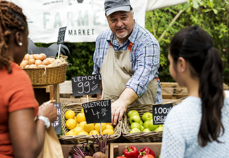 Greengrocer selling organic fresh agricultural product at farmer market Stok Fotoğraf - 90813447