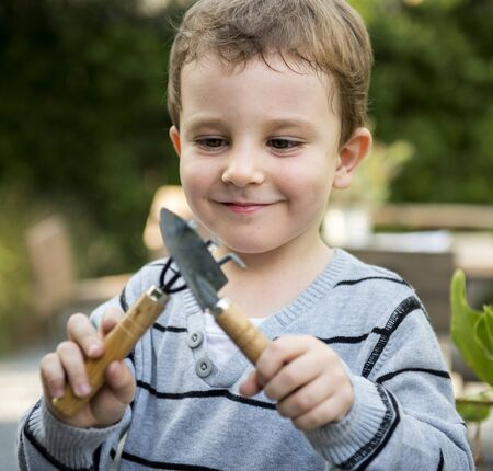 Cute young boy playing with gardening tools
