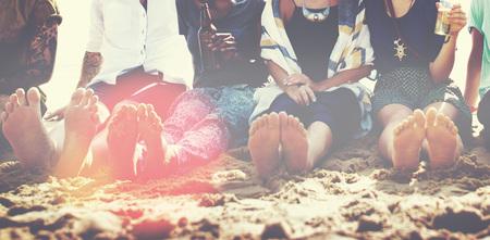 Vrienden die in het zand op een strand zitten Stockfoto