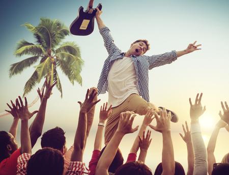Jonge man met een gitaar die op een strandconcert Stockfoto