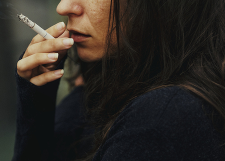 Woman smoking cigarette alone Stock Photo