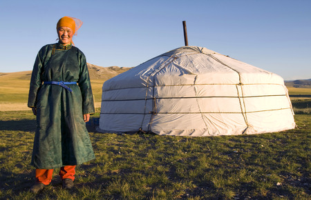 Mongolian woman standing in front of a ger