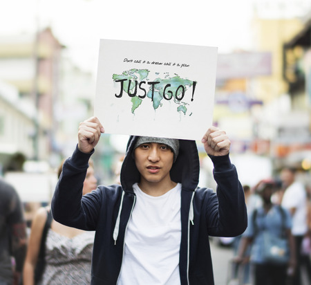 Young asian guy with a Just Go placard